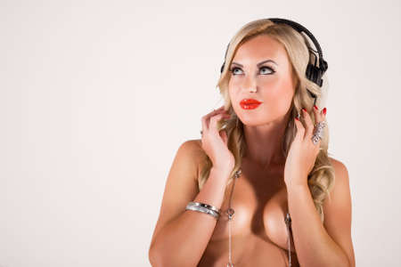 sexy headphones: Portrait of a sexy blonde who listens to music on headphones on a white background