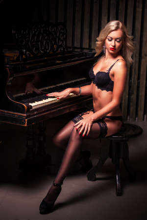 pianista: mujer rubia sexy en ropa interior negro sentado cerca de piano Estudio de moda retrato