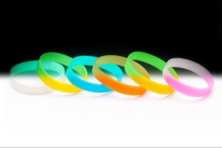 Colored latex glowing light-bracket bracelet on Black Background. Multicolor set