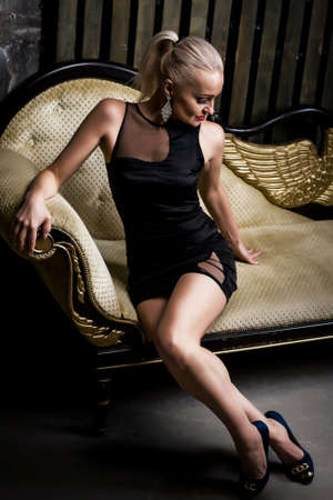 Sexy blonde woman in short black dress sitting on the couch.