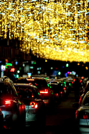 Bright circles from streetlamps and car's headlights on defocused photo of night street. Blurred Defocused Lights of Heavy Traffic