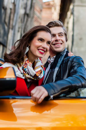 Romantic couple is standing near orange modern car on the street. Handsome smiling young man and attractive woman in a red coat. Love story Stock Photo