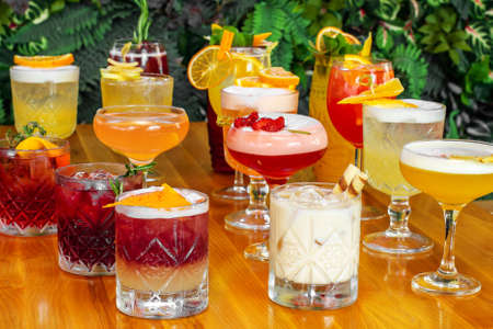 Set of alcoholic multicolor cocktails with fruits on the wooden table.