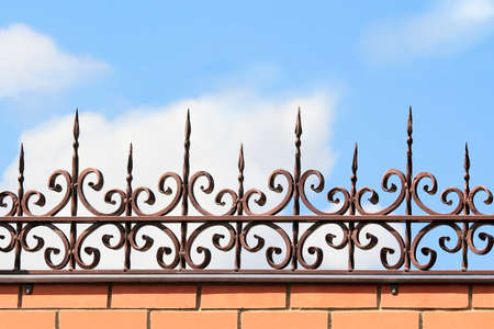 workmanship: Metal forged fence on a brick wall on the background of blue sky