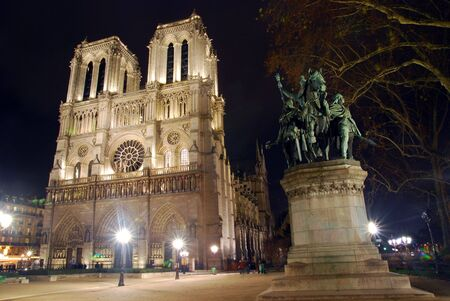 Notre Dame Church at night with a statue
