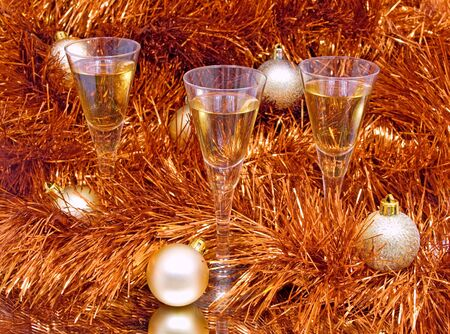 three glasses and Christmas balls are on the mirror