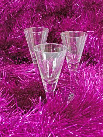 Three empty glasses are in the purple tinsel  Stock Photo