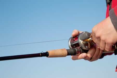 The fisherman with a baitcasting reel photo