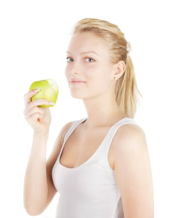 Young blonde with apple isolated on white. Focus on girl`s eyes.