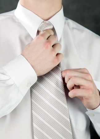 Businessman is adjusting his tie  on gray background