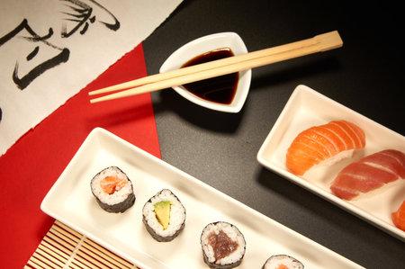 asian food sample with sushi, sashimi, chopsticks and soy dressing.