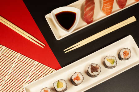 white plates of sushi and sashimi with sake and chopsticks in a compassion on a black and red background
