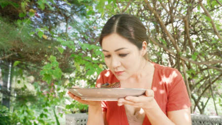 A hungry woman holding a plate with grilled octopus, smelling the seafood dish and closing eyes in rapture. A woman in a green garden of restaurant looking on a BBQ platter greedily and happily. Lunch
