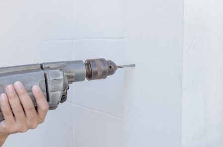 Craftsman drilling holes into the white wall with drill photo