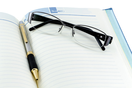 Black glasses and silver pen on open book with isolated background photo