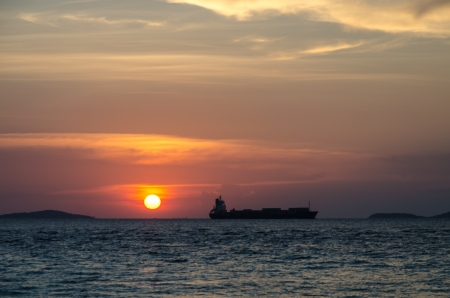 Sunset with cargo ship at Samae Beach, Koh Larn, Pattaya, Chonburi, Thailand photo