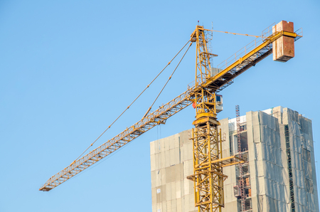 Industrial construction crane are operating over blue sky photo