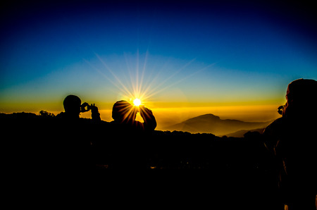 Silhouette of tourists  taking photographys in a sunrise photo