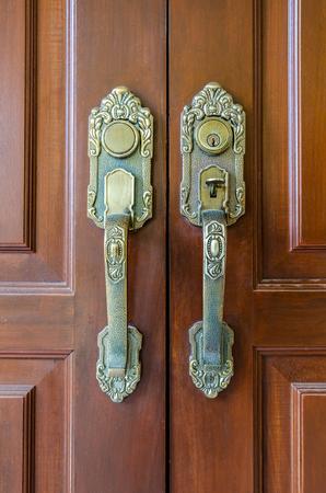 Metal door handle vintage style over wooden door photo