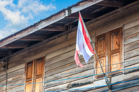Old Thai flag in front of Thai house in rural photo