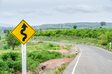Twisty road with roadsign in nature photo