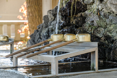 purification: Brass dipper arranged in front of Purification trough in Shinto shrines and Buddhist temple, Japan Stock Photo