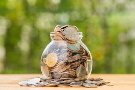 spilling: Thai baht coins spilling out of money jar