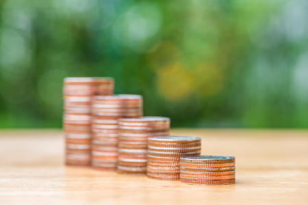 growth business: Stack of coin on wood table and blur background, selective focus