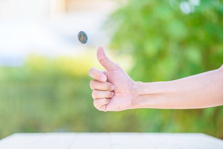 coin toss: Hand of woman is flipping a coin Stock Photo