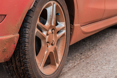 dirty car: Dirty wheel of red car Stock Photo