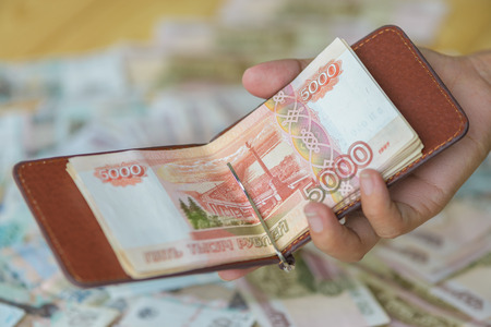 Womans hand holding leather money clip wallet with bank notes roubles, Russian big money.