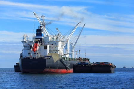 Loading containers to international container cargo ship in the ocean.