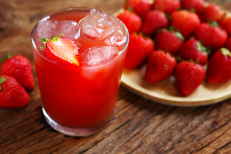 Strawberry juice with ice on the table. Shooting in studio for advertising concept.