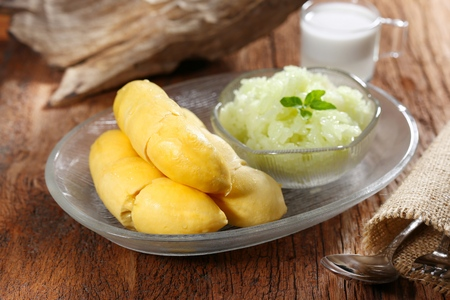 Thai dessert Sticky rice durian. Durian the king of fruits served with sticky rice and fresh coconut milk topping, selective focus and toned image. Still life photography in studio