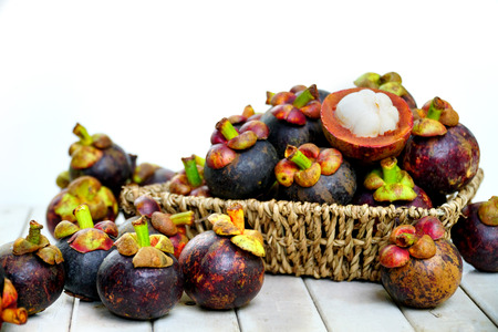 Still life photography of Thai fruit: Mangosteen is queen of fruits. Organic mangosteen is popular fruits, Organic fruit on wooden plate. Isolated on white background. Clean food good taste idea concept.
