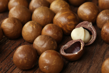 Roasted macadamias on wooden table, selective focus and toned image. Healthy food concept, free space for text. 免版税图像