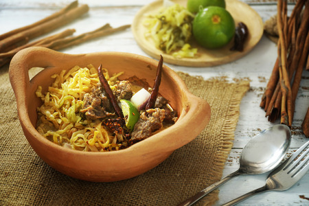Still life photography of food: Khao Soi, Yellow noodles with beef curry served with crispy noodle and vegetables. Traditional food of Northern Thailand. Shooting in studio, Clean asian food ideas.