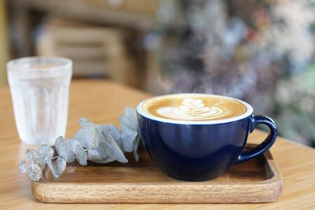 Hot coffee on wooden table, The best cappuccino fresh coffee with smoke. Porcelain coffee cup on table, Selective focus and free space for text. Industrial food and drink concept.