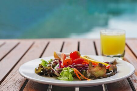 Vegetable salad served with pineapple juice on the table side pool. clean food and healthy concept. selective focus and free space for text.