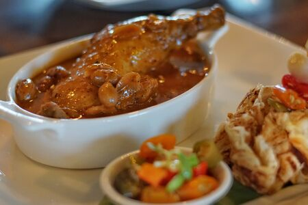Massaman Curry is popular Thai food. Chicken curry with coconut milk, chili, and spicy herbs. Served in pie, eating with steam jasmine rice. Selective focus. Still life shoot in restaurant. Stockfoto