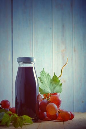 Grape juice in glass bottle, organic fresh grapes on background, The best of drink for healthy and holiday celebration ideas concept, free space for text. Vintage toned image.