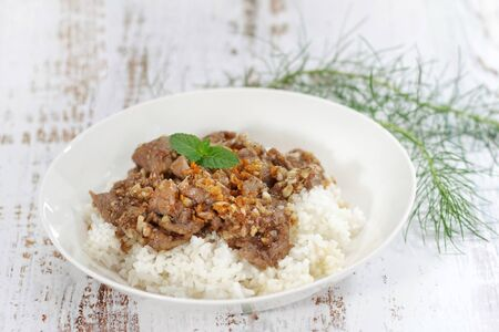 Stirred and fried pork with garlic and pepper served on steamed rice. Shooting in studio on backdrop for advertising. Thai and Asian food concept. Stockfoto
