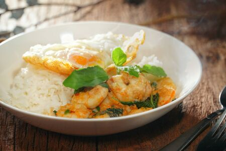 Thai food : Kaphrao Kung is Stirred and fried shrimps with holy basil and chilies served on steamed rice and fried egg. Shooting in studio for advertising. Thai and Asian food concept.