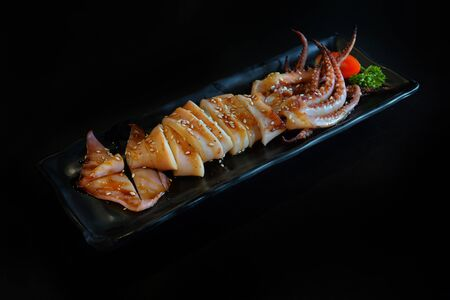Japanese food: Grilled squids with sauce served with Japanese cooked rice on table. Clean food concept. Toned image. Selective focus and free space for text.