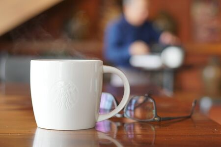 Hot coffee on wooden table, The espresso prefect shot, fresh coffee with smoke. Business time with coffee, selective focus and free space for text, Industrial food and drink concept.