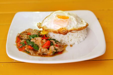 Thai food : Kaphrao Moo is Stirred and fried pork with holy basil and chilies served on steamed rice and fried egg. Shooting in studio for advertising. Thai and Asian food concept.