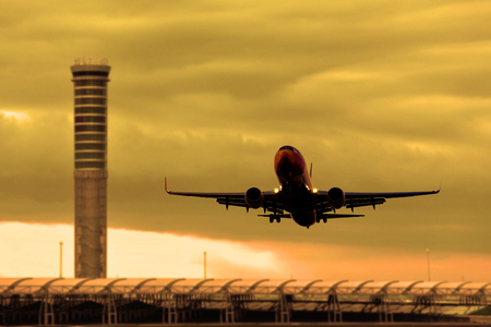 Silhouette of airplane in cloudscape. Low angle shot of The airplane flying across camera in beautiful sky. Transportation by airplane concept. Redactioneel