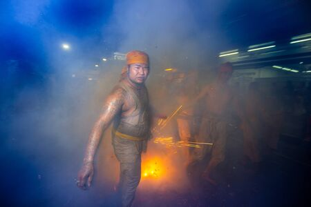 CHONBURI, THAILAND - SEPTEMBER 30, 2019: At night, The parade possessed by his god walking on fire in Vegetarian Festival also known as Nine Emperor Gods Festival. Stop action and motion blur. Editorial