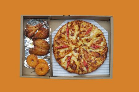 Pizza, fish rings and grilled chicken wings in paper box isolated on orange background. This image stacked with clipping path for advertising. ideas concept.