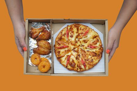 Hand holding pizza, fish rings and grilled chicken wings in paper box isolated on orange background. This image stacked with clipping path for advertising. ideas concept.
